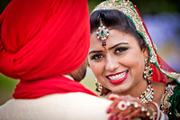 Indian Bride smiling with groom opposite direction